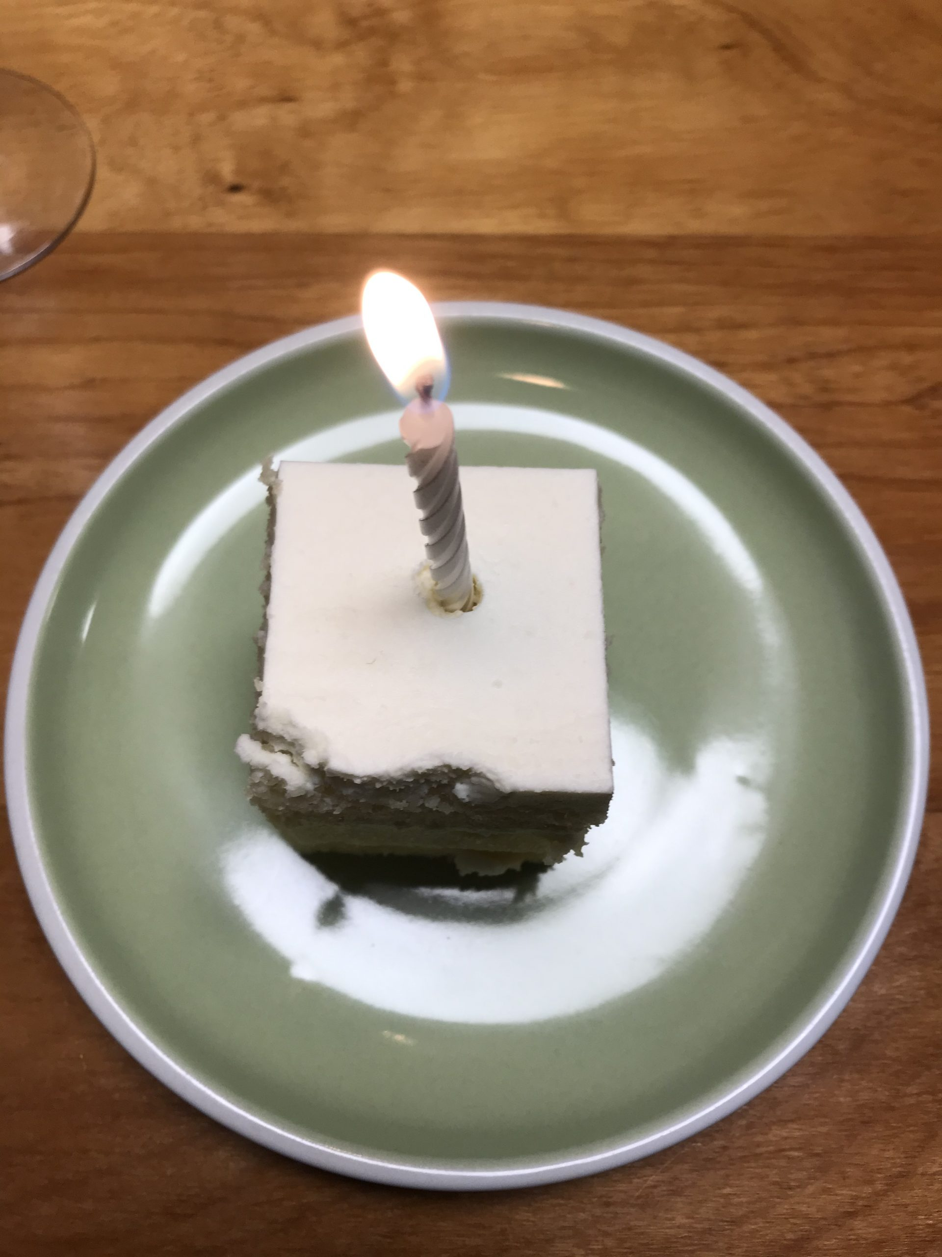 Slice of lemon birthday cake with candle